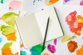 Fotografie top view of white notebook with pencil on background with abstract watercolor paintings