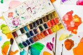 pohled shora barev a štětce na papírech s abstraktní akvarel skvrny