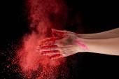 Fotografie cropped view of adult woman holding red holi powder and clapping on black background
