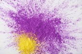 top view of explosion of purple and yellow holi powder on white background