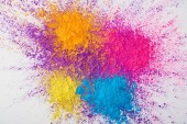 Fotografie top view of explosion of multicolored holi powder on white background