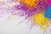 pohled shora výbuchu žluté, fialové, oranžové a modré holi prášku na bílém pozadí