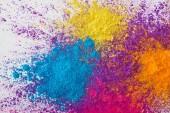 Fotografie Draufsicht der Explosion von gelbem, violettem, orangefarbenem und blauem Holi-Pulver auf weißem Hintergrund
