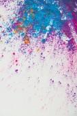 pohled shora výbuchu fialové a modré holi prášku na bílém pozadí