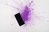Fotografia top view of smartphone with blank screen and explosion of purple holi powder on white background