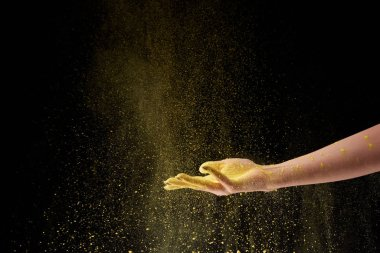 cropped view of woman holding yellow holi powder on black background