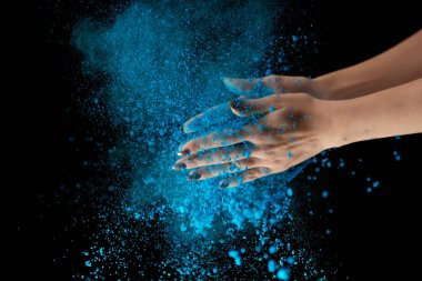 cropped view of adult woman holding blue holi powder and clapping on black background