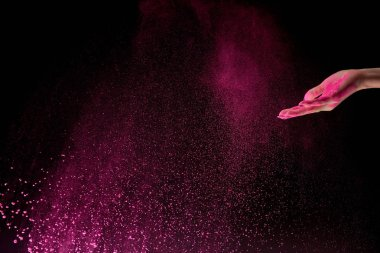 cropped view of adult woman with pink holi powder in air on black background