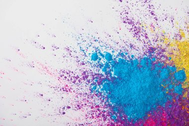 top view of explosion of yellow, purple and blue holi powder on white background