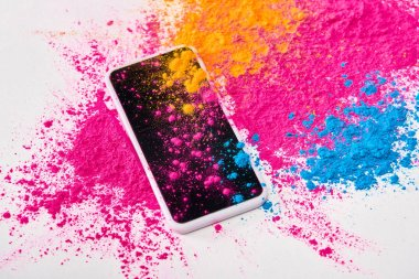 top view of smartphone and explosion of multicolored holi powder on white background
