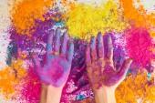 oříznutý pohled ženy ukazující ruce v prášku vícebarevné holi