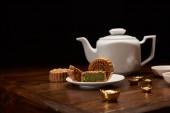 hagyományos finom kínai mooncakes, teáskanna és a fából készült asztal elszigetelt fekete arany rúd