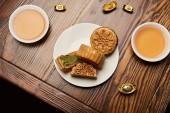 Fotografie traditionelle Mondkuchen mit Teetassen und Goldbarren auf Holztisch