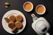 Fotografie Draufsicht des Mooncakes, Tassen und Teekanne isoliert auf schwarz
