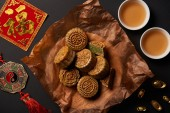 Photo top view of traditional mooncakes with chinese talismans and tea isolated on black