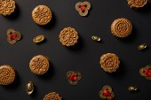 Fotografia top view of traditional mooncakes and feng shui coins isolated on black
