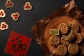 pohled shora na tradiční mooncakes s čínskými talismany izolované na černém