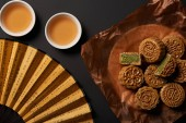 Fotografie top view of traditional chinese mooncakes with tea and hand fan isolated on black