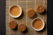 top view of traditional mooncakes and tea cups on bamboo table mat
