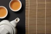 pohled shora konvice se šálky a bambusové prostírání s kopií prostor