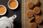 top view of traditional mooncakes, tea pot and cups on bamboo table mat