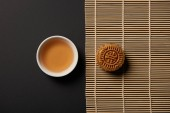 top view of mooncake and cup of tea on bamboo table mat
