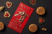 Fotografie Draufsicht der traditionelle Mondkuchen mit chinesischen Hieroglyphen und Feng Shui Münzen isoliert auf schwarz
