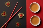 top view of chopsticks with traditional chinese tea and feng shui coins on red and black background