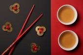 Fotografie pohled shora na hůlky s tradiční čínské čaje a feng shui mince na červené a černé pozadí