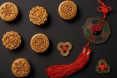 Fotografia top view of traditional mooncakes with chinese talismans isolated on black