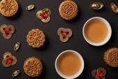 Fotografie Draufsicht der traditionellen Mooncakes, Teetassen und Feng Shui Münzen isoliert auf schwarz