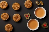 Fotografia top view of traditional mooncakes, tea cups and feng shui coins isolated on black