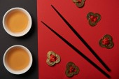 top view of tea cups, feng shui coins and chopsticks on red and black background