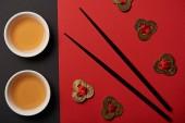 Fotografie pohled shora na čajové šálky, feng shui mince a hůlky na červené a černé pozadí