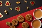Fotografie Draufsicht des Mooncakes, Feng Shui Münzen und Tassen mit Tee auf roten und schwarzen Hintergrund