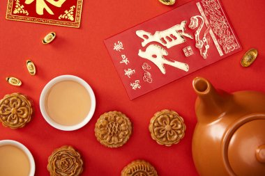 Top view of traditional mooncakes with chinese hieroglyphs and tea isolated on red stock vector