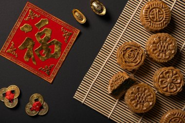 top view of traditional mooncakes with chinese talismans and bamboo table mat isolated on black