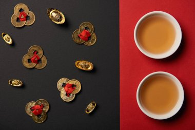 top view of tea cups and feng shui coins on red and black background