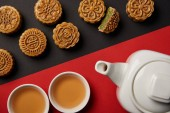 top view of mooncakes, tea pot and cups on red and black background