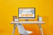 Fotografie Počítač s obsah marketing nápisy na dřevěný stůl na žlutém podkladu