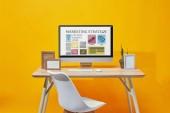Počítač s marketingové strategie webové stránky na obrazovce na dřevěný stůl na žlutém podkladu