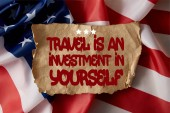 Fotografie vintage crumpled paper with travel is an investment in yourself quote on american flag