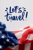 Fotografie top view of united states of america flag and lets travel lettering on white surface