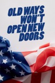Photo top view of united states of america flag and old ways wont open new doors quote on white surface