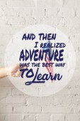 cropped image of man holding american flagpole against white brick wall with and then i realized adventure was the best way to learn quote