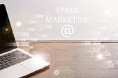 Fotografie Nahaufnahme der Laptop auf Holztisch mit Symbolen und e-Mail-Marketing-Schriftzug