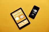 Fotografia vista superiore del digital tablet e smartphone con marketing strategia ed e-mail app sullo schermo su priorità bassa gialla