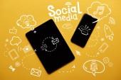 Fotografie pohled shora digitálních tablet a smartphone s sociální media ilustrace na žlutém podkladu