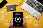 oříznutý pohled člověka drží digitální tablet s e-mailové marketingové ilustrace