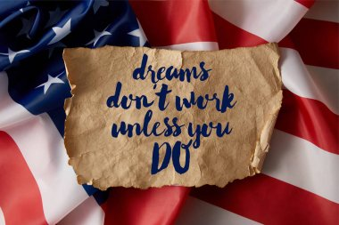 vintage crumpled paper with dreams dont work unless you do quote on american flag